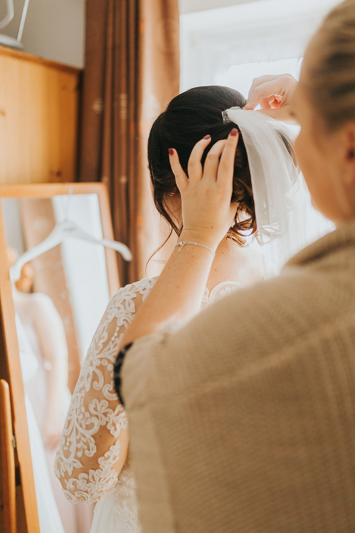 bridesmaid adjusts brides veil wedding